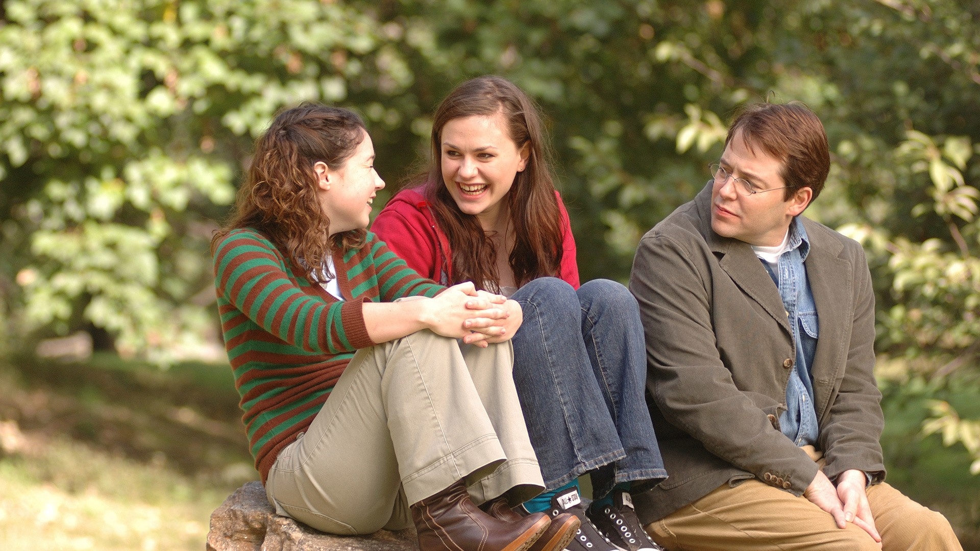 Sarah Steele, Anna Paquin and Matthew Broderick in Margaret (2011). Lisa sits on a large rock in the park with her friends Becky and her teacher John. Lisa and Becky are laughing together whilst John looks on solemnly.